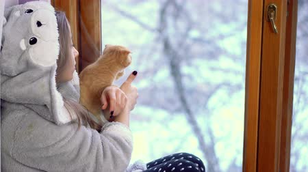 Young girl holds kitten at home. She sits by window on the window in warm dressing-gown. Winter in street. Lop-eared cat.