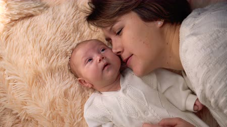 Young mother and newborn daughter lie on a white blanket. Woman talks and kisses child. Happy childhood.