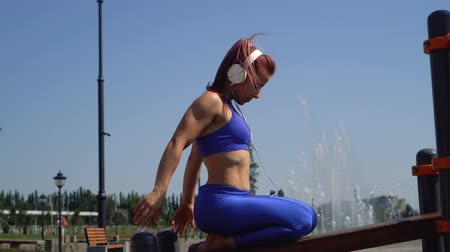 Slender girl on outdoor workout. She does warm-up of hands. Woman in sportswear and barefoot sitting on sports field. She listens to music on headphones. Dostupné videozáznamy