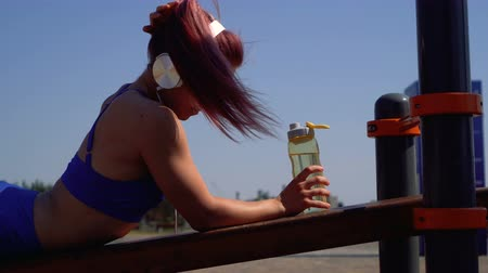 Slender girl on outdoor workout. She rests, puts on headphones and listens to music. Woman holding a bottle of water Dostupné videozáznamy