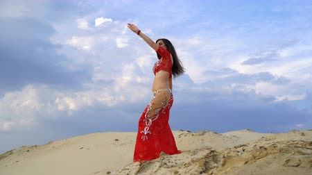 Oriental beauty dances belly dancing outdoors. Attractive girl in a red dress is dancing in the desert in the background sky with clouds.