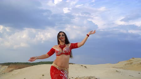 Oriental Beauty dancing sensual belly dance outdoors. Attractive girl in a red dress is dancing in the desert in the background sky with clouds. Dostupné videozáznamy