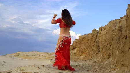 Oriental Beauty dancing sensual belly dance outdoors. Dance of seduction. The girl shows femininity and grace in the dance.
