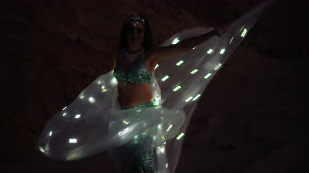 dune : Oriental beauty dancing belly dance with glowing wings. Delightful and alluring grace of movements. Girl dancing in the desert at sunset.