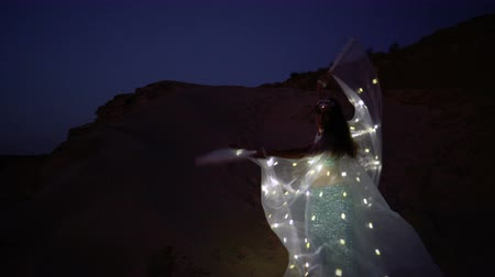 butterflies in the stomach : Oriental beauty dancing belly dance with glowing wings. Delightful and alluring grace of movements. A girl dancing at night in the desert.