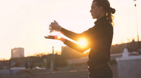 manipulacja : Contact juggling. Man juggle clear acrylic ball at sunset. Magic movement. Performance on street.