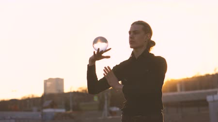manipulacja : Contact juggling. Man juggle clear acrylic ball at sunset. Magic of movement. Performance on street.