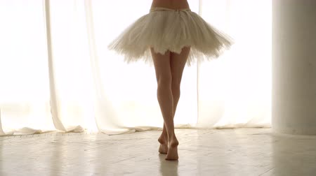 Slender legs and hands of dancer close-up. Girl trains barefoot and in tutu. Ballet dancer in rehearsal. Graceful hand movements. Classic ballet. Dostupné videozáznamy