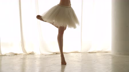 Slender ballerina rehearses. Girl trains barefoot and in tutu. Ballet dancer. Graceful movement. Classic ballet.