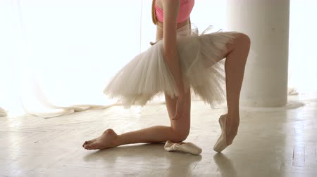 Slender ballerina rehearses. Girl in tutu wearing pointe shoes. Ballet dancer. Graceful movement. Classic ballet. Dostupné videozáznamy