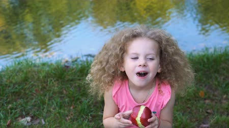 Little curly cute girl eating red apple outdoors. She enjoys a taste of ripe fruit. Dostupné videozáznamy