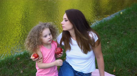 Family picnic by lake. Mother and daughter outdoors. Curly cute little girl eating red apple.