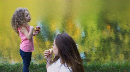 Family picnic by lake. Mother and daughter outdoors. Curly cute little girl holding a red apple and telling story. Woman is surprised.