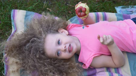 Little curly cute girl eating red apple outdoors. She enjoys a taste of ripe fruit lying on a striped mat.