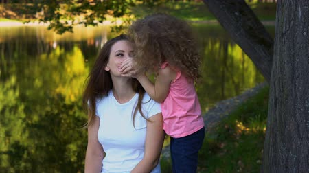 Family time. Mother and daughter are resting by lake. Little girl covers her mouth to woman. Daughter kisses her mother and waves her head.