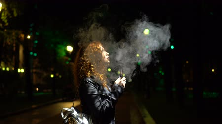 Girl smokes electronic cigarette on the street at night. She quits smoking. Non-nicotine cigarette.
