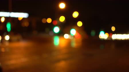Bokeh night streets of the city. Out of focus. Houses, signs and cars. Busy traffic on the city highway. Blurred urban background.