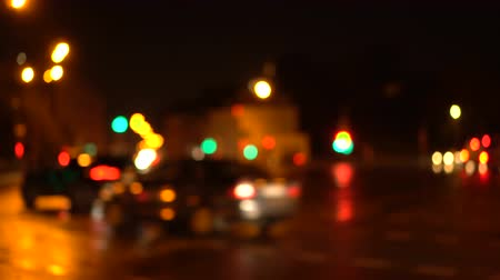 Bokeh night city streets. Out of focus. Houses, neon signs and cars. Busy traffic on the city highway. Headlights. Blurred urban background.
