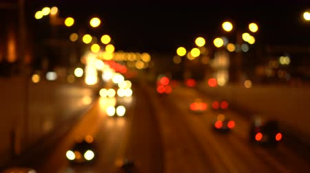 Bokeh night city streets. Out of focus. Busy traffic on the city highway. Headlights. View from above. Blurred urban background. Dostupné videozáznamy