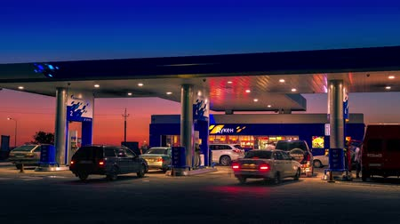 gazprom : Day into night time, cars refuel at the gas station Gazpromneft in Kazakhstan. Timelapse