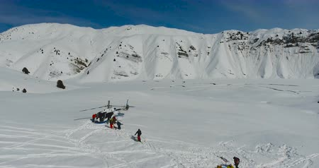 ledovec : Skiers and snowboarders board a Helicopter in the winter mountains. Aerial view, camera slide down.