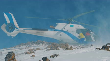 evacuation : The helicopter landed in the mountains in winter, raising a cloud of snow