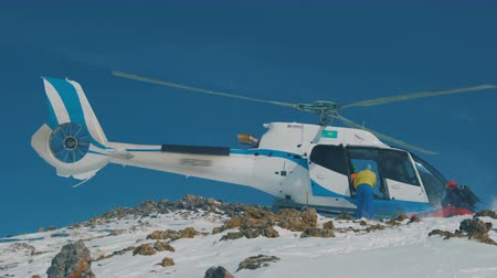 evacuation : Heliskiing Skiers are disembarked from the helicopter in the mountains in winter. Close up view.