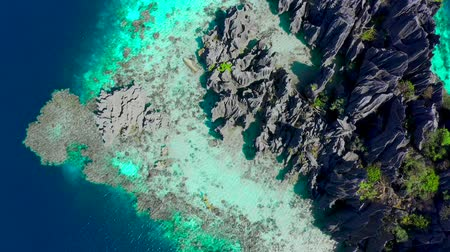 canoa : Aerial top view flying amazing rocks and tropical coral reef lagoon. Kayak are sailing on the sea. Coron, Busuanga, Philippines.
