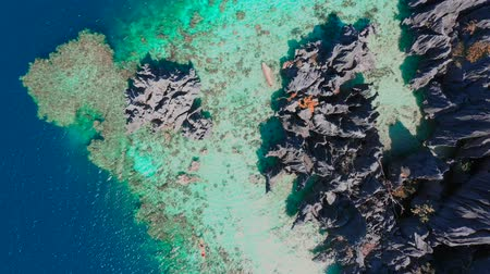 Aerial top view flying amazing rocks and tropical coral reef lagoon. Kayak are sailing on the sea. Coron, Busuanga, Philippines.
