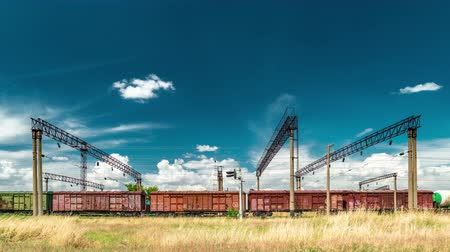 Freight railroad hopper train at the background clouds. Timelapse 4K