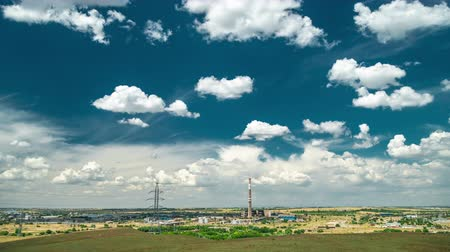 Industrial landscape with power plant with yellow field and big blue clouds. Timelapse 4K Wideo