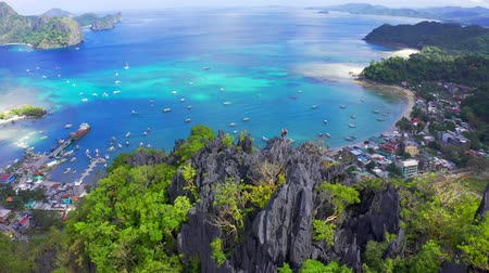 bergbeklimmer : Man and woman standing on a rocky top of the mountain overlooking the port and the blue sea lagoon in El Nido, Palawan, Philippines.