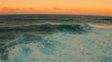 Colorful Ocean Wave. Sea water in crest shape. Sunset light and beautiful cloudscape sky
