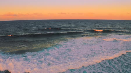 Powerful wave breaks along the shore at beautiful sunset time