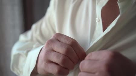 A man dresses in a shirt Stock Footage