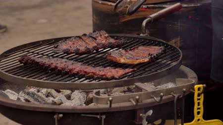 A man prepares pork ribs on the grill