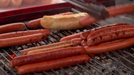 Sausages for hot dogs are roasting on the grill