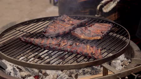veal recipes : A man prepares pork ribs on the grill