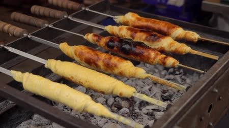 Georgian traditional dish - khachapuri, pastry with cheese rotating on a skewer fried on the grill. Cooking food.