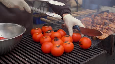 The cook turns over the tomatoes on the grill.