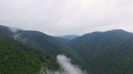 Aerial View. Flying over the high mountains in beautiful clouds . Aerial camera shot. Wideo