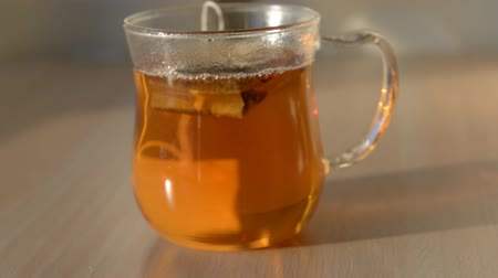 teabag : pouring hot water over tea bag in transparent glass cup