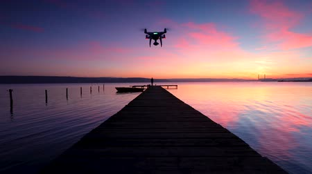 stilles wasser : Aerial drone flight over small dock and boat at the lake. Beautiful sunset.