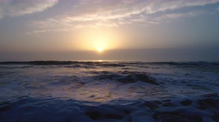 horizonte sobre a água : Aerial view of beautiful sunrise over the sea. Splashing waves.