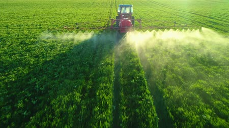 cultivo : Aerial view of farming tractor plowing and spraying on field