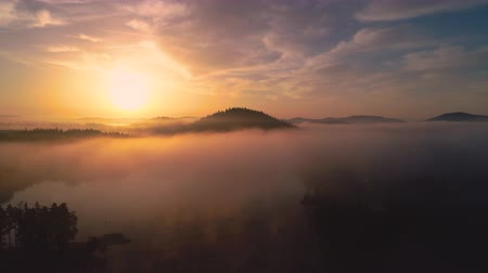 cam : Aerial sunrise view of morning fog on the lake in the mountain