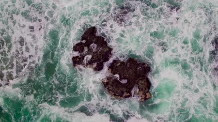 скалистый : Aerial view of rocky coastline with crashing waves.