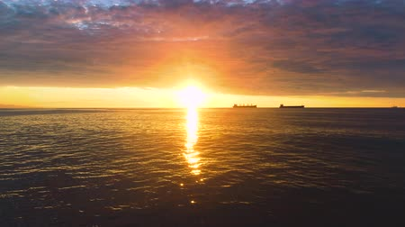 navigovat : Cargo ships sailing in still water near port of Varna, Bulgaria. Beautiful sea sunrise.