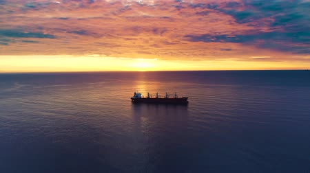 yelkencilik : Cargo ship sailing in still water near port of Varna, Bulgaria against sun. Beautiful sea sunrise.