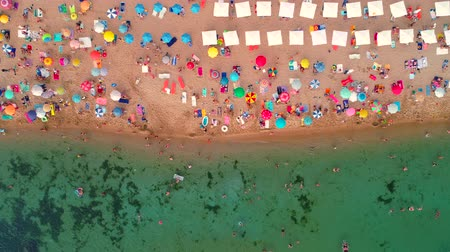 parasol : Aerial top view on the beach. Umbrellas, sand, people and sea waves Stock Footage